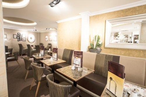 Belichtetes Café mit Sitzbänken und Tischen