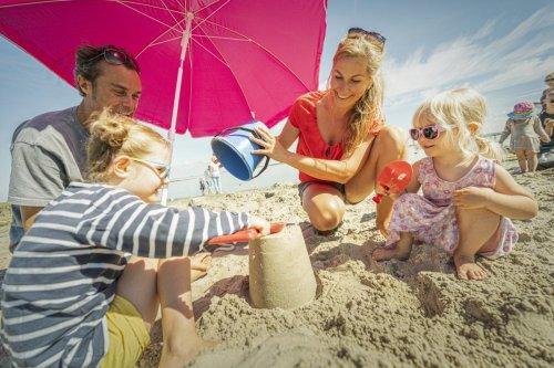 Familie spielt im Sand an der Badestelle Lundenbergsand