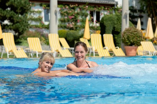 Girlfriends swim in thermal water