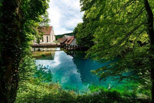 Ein tiefblauer See, in dem sich die Wolken und Bäume ringsherum spiegeln. Am einen Ende ist ein kleines Haus mit Mühlrad.