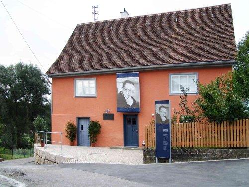 An einem orangenes Wohnhaus mit kleinem Garten davor und blauen Türen hängt ein Banner mmit einer Person darauf. Auf einem Schild an der Hofeinfahrt ist die Person ebenfalls abgebildet und es stehen weitere Infos darauf.