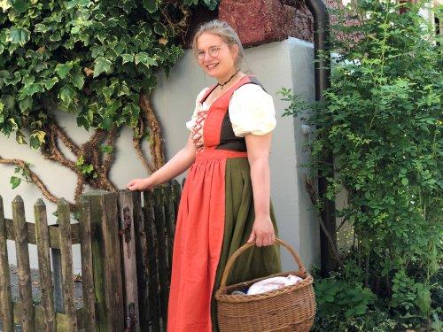 Schankmagd Josepha steht in der Salzgasse Pfullendorf mit Körbchen an einem Zaun