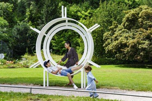 Frau mit Kindern  auf der Modified Social Bench im grünen Kurgarten