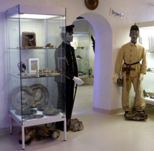 Sichtbar ist ein Teil des Museums, mit einer Vitrine mit Ausstellungsstücken und nebendran zwei Puppen in typischen Bergwerks-Kleidern.