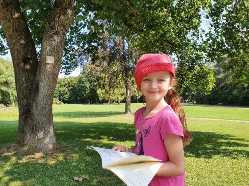 Mädchen mit Zinkenpfadheft steht vor einem Baum mit Zinken