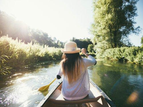 Eine Frau sitzt in einem Kanu und paddelt entlang einem Fluss. Vom Ufer ragen Pflanzen über den Fluss. Sie trägt einen Sonnenhut.