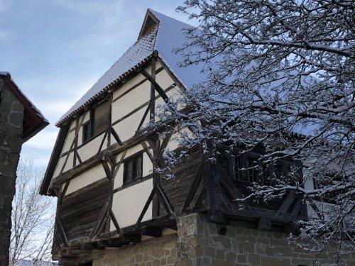 Das alte Fachwerkhaus mit schneebedecktem Dach.