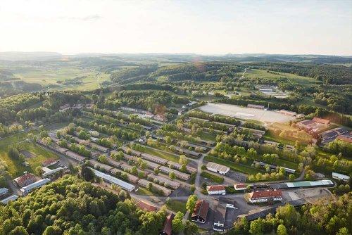 Ein Areal mit mehreren Gebäuden, die systematisch angeordnet sind, Bäumen und Wald sowie einer großen Asphalt-Fläche von oben. Im Hintergrund die weite Landschaft. Die Sonne taucht alles in ein stimmmungsvolles Licht.