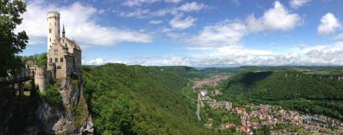 Ein Schloss mit einem großen weißen Turm und dessen Fassade kunstvoll verziert ist, steht auf einem Fels. Davor ist eine Brücke, die zur anderen Seite führt. Auf der rechten Bildhälfte ist ein Ausblick über ein Tal mit einer Stadt. Drumherum ist Wald.