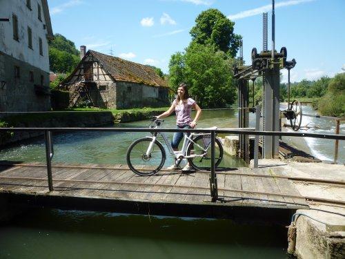 Eine Frau mit dem Rad auf einem Stauwehr.
