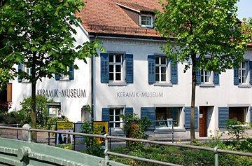 Blick von einer kleinen Brücke auf das von Bäumen gesäumte Keramikmuseum