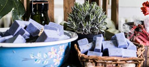 Schalen und geflochtene Körbe sind mit lila rechteckigen Seifen gefüllt. Dahinter stehen weitere Produkte und Pflanzen zur Dekoration.