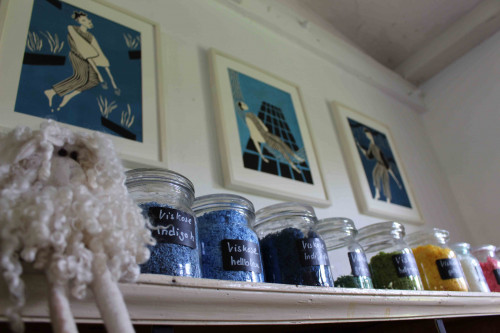Auf einem kleinen Brett an der Wand stehen verschiedene Weckgläser mit bunten Fasern. Jedes Glas ist beschriftet. Darüber hängen an der Wand drei Bilder.