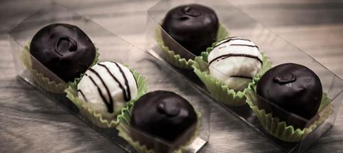 Auf einem Tisch stehen kunstvoll angerichtete Pralinen in brauner und weißer Schokolade. Sie liegen in einer Plastikschale.