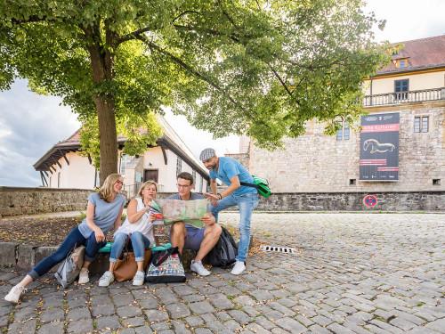 Eine kleine Gruppe sitzt vor einem Baum im Vorhof des Museums Schloss Hohentübingen