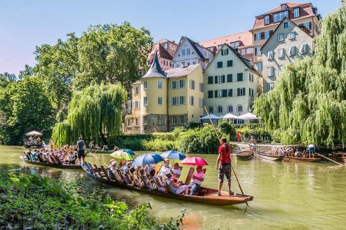 Vollbesetzte Stocherkähne auf dem Neckar vor dem Hölderlinturm in Tübingen