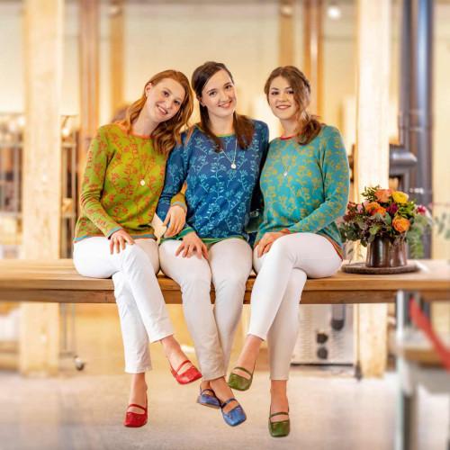 Drei Personen sitzen auf einem Tisch und lächeln in die Kamera. Daneben steht eine Vase mit bunten Blumen. Alle tragen eine weiße Hose und bunte Pullover. Die gleichen Schuhe haben ebenfalls verschiedene Farben.