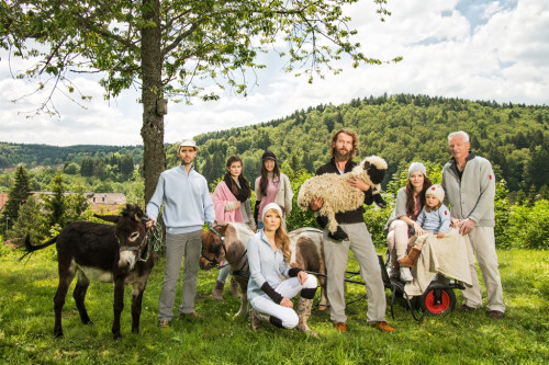 Mehrere Personen auf einer grünen Wiese mit einem Esel, Ponny und Schaf. Sie posieren für die Kamera. Es ist sonnig.  Hinter ihnen steht ein Baum.