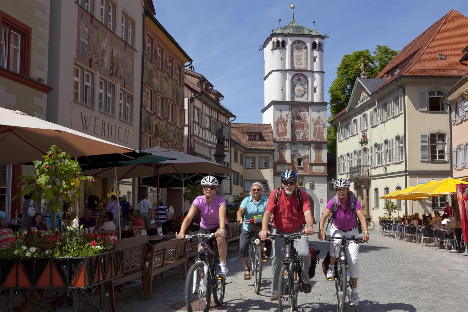 Radfahrerguppe durchquert die historische Altstadt in Wangen und das Frauentor
