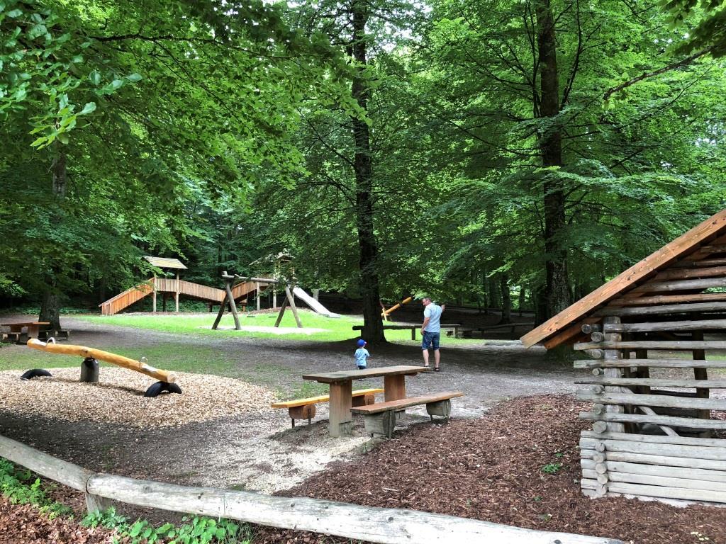Waldspielplatz mit Sitzgelegenheiten und Spielhäuschen
