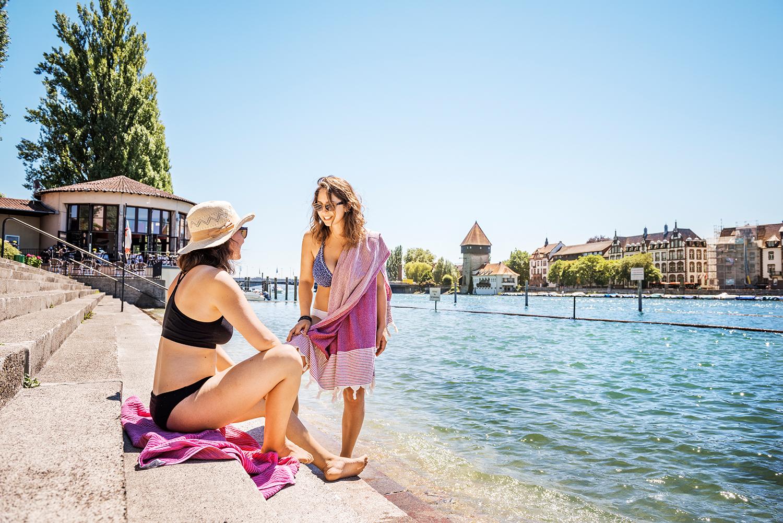 Zwei Frauen unterhalten sich auf den Stufen des Rheinstrandbades