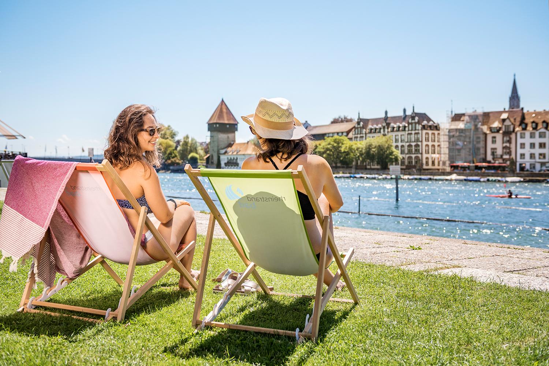 Zwei Frauen in Liegestühlen genießen die Aussicht aufd en Rhein