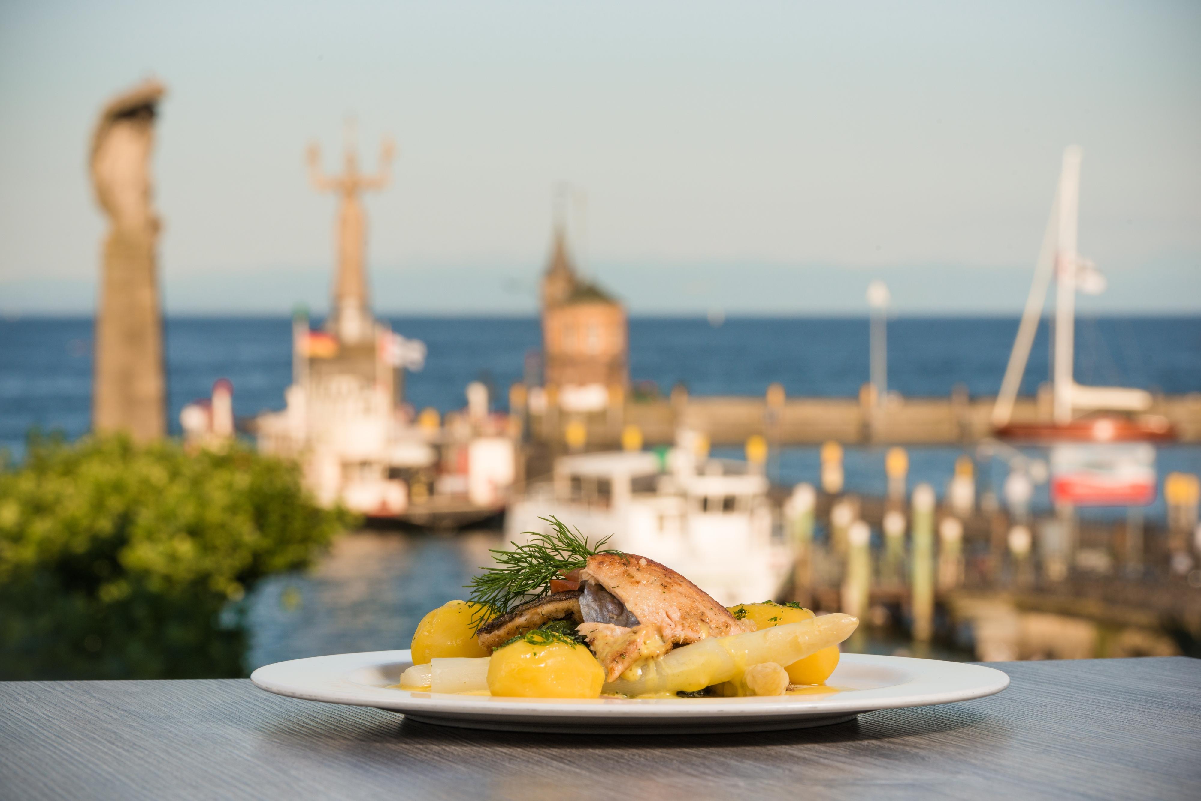Gebratener Fisch auf Spargel und Petersilienkartoffeln vor dem Konstanzer Hafen